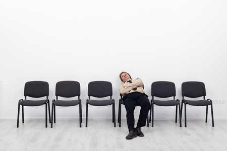 Bored and disappointed employee sitting in waiting room on a row of chairs Фото со стока