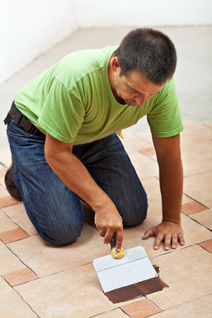 Construction worker testing the joint color on ceramic tiles floor - spreading it with a spatula photo