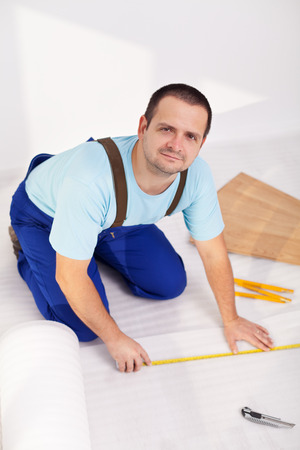 redecorate: Man laying laminate floor at home - measuring and cutting the isolation layer