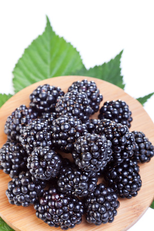 black berry: Blackberries on wooden plate - top view, isolated Stock Photo