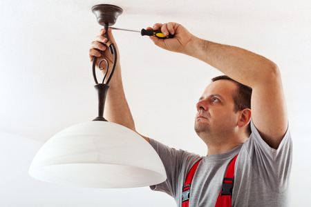 installation: Electrician mounting ceiling lamp - installing the wires mask