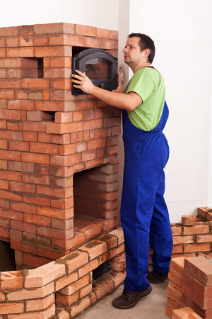 Worker building a masonry heater - trying on and fitting the top oven door photo