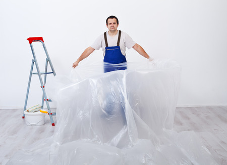 foil roll: Worker preparing to paint a room - laying protective plastic film layer Stock Photo