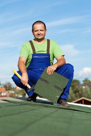 shingles: Worker installing bitumen roof shingles in summer time