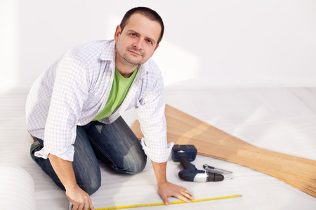 Man preparing to install laminate floor planks photo