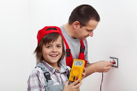 Montage: Gl�cklicher Junge half seinem Vater Montage von elektrischen Wandleuchten - h�lt das Multimeter