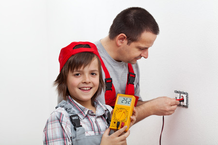 Happy boy helping his father mounting electrical wall fixtures - holding the multimeter photo