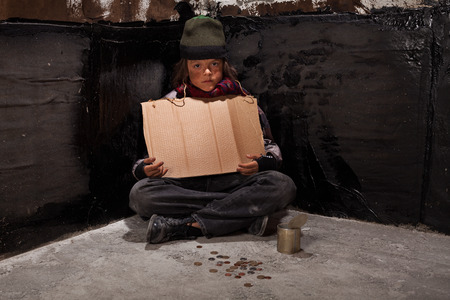 Begging homeless child sitting with a blank sign and some change in a dark corner Standard-Bild