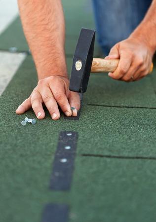 Werknemer installeert dakshingles - close-up op de handen met spijkers en hamer