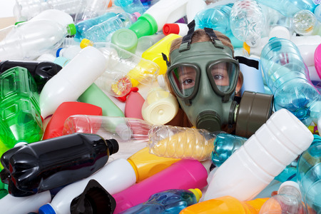 Child with gas mask covered with plastic bottles waste Stock Photo