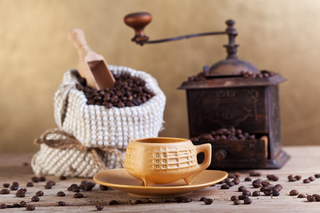 Coffee beans in a bag standing on a table with old grinder and cup photo