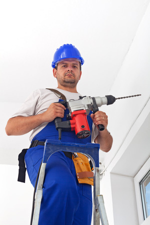 Worker with power tool standing on ladder ready to drill a hole photo