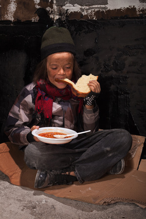 Young dirty homeless boy eating on the street sitting on cardboard