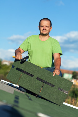 shingles: Roofer on top of building with bitumen roof shingle