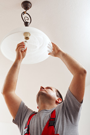 finished: Electrician finished mounting ceiling lamp - installing a fluorescent lightbulb Stock Photo