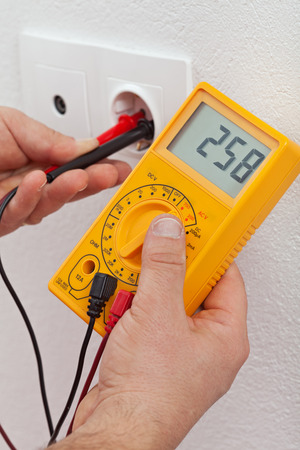 outlets: Electrician hands measuring voltage in electrical outlet - closeup Stock Photo