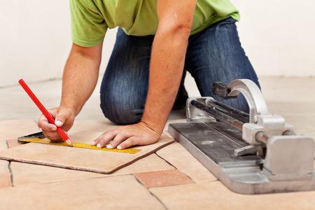Werknemer handen leggen van keramische vloertegels - meten en markeren een stuk Stockfoto