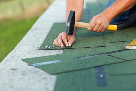 Manos de los trabajadores que instalan las tejas del techo de betún - primer plano en las manos con un martillo y clavos