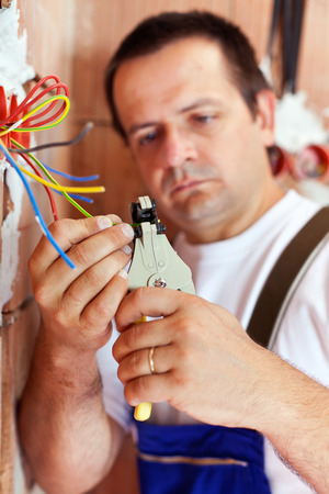 27002646: Electrician peeling wire endings in new building - focus on hands Stock Photo