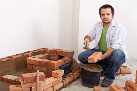 firebox: Man building a brick stove or fireplace - with bricks, trowel and clay mortar