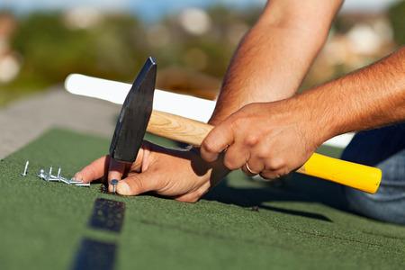Man Hände Befestigungs Bitumen-Dachschindeln mit Nägeln und Hammer - Seitenansicht