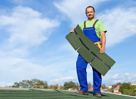 Worker putting bitumen shingles on a roof - standing on top of building