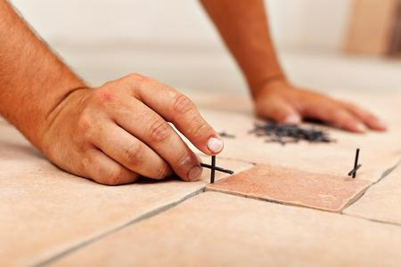 floor covering: Worker hands placing spacers between ceramic floor tiles - close up Stock Photo