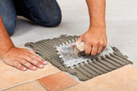 tile adhesive: Worker hands spreading adhesive for ceramic floor tiles - closeup