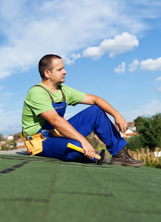 Roofer worker resting on top of building - sitting on bitumen roof shingles photo