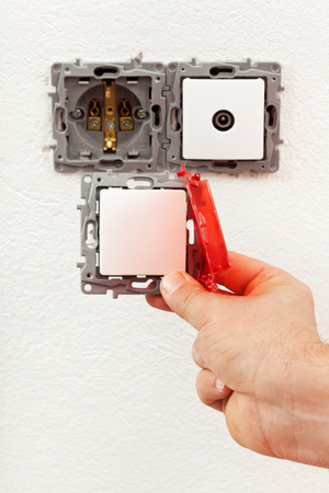 Changing a defective electrical wall fixture - male hand with a new switch