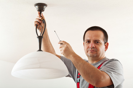Electrician mounting ceiling lamp - closeup