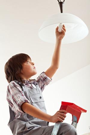 Boy installing an energy saver lightbulb - resources awareness concept photo
