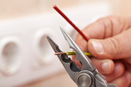 electrician tools: Pliers peeling copper wires - closeup on electrician hands, wall sockets in the background