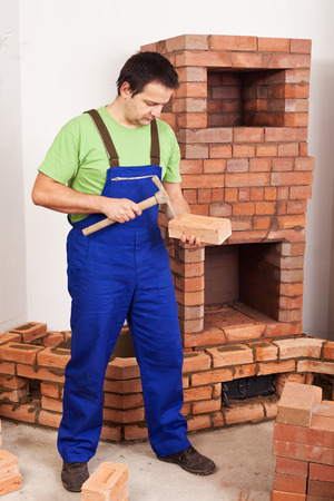 firebox: Man building masonry heater - shaping a brick to fit the structure