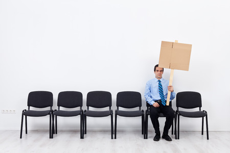 Businessman protesting alone - sitting on chairs row with blank sign Stock Photo