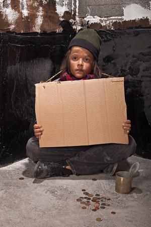 niños pobres: Muchacho pobre mendigo en la calle con una mirada fija la celebración de firmar en blanco cartón - copia espacio