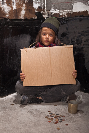 in need of space: Poor beggar boy on the street with a blank stare holding cardboard sign - copy space