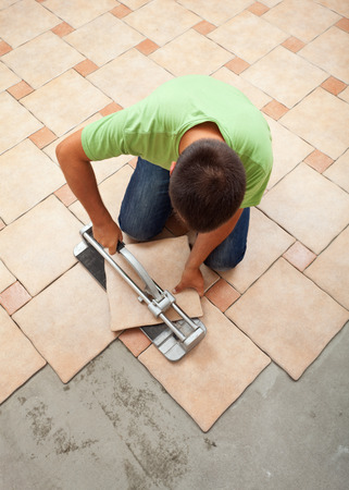 Worker cutting ceramic floor tile - top view of the work site Stock Photo - 28351414