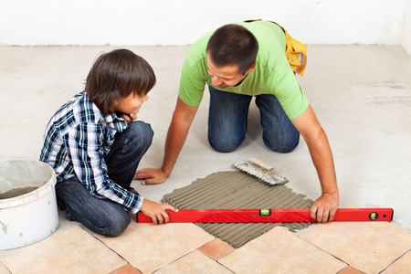 tile adhesive: Man and boy laying ceramic floor tiles together - checking their work with a spirit level