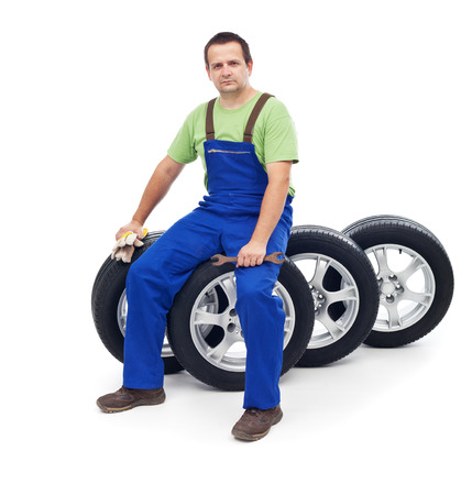 Friendly car mechanic sitting on tires - isolated