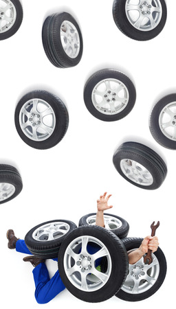 the unskilled worker: Car mechanic on the flor covered with tires - overwhelmed by a technical issue concept