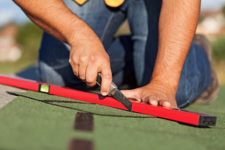 dach: Arbeiter installieren Bitumen Dachschindeln - Nahaufnahme auf Händen Lizenzfreie Bilder