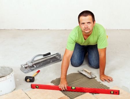 Man laying ceramic floor tiles on concrete floor - checking his work with a spirit level Stock Photo - 28351383