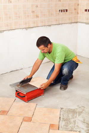 Man cutting ceramic floor tiles - laying them on the concrete floor Stock Photo - 28351384