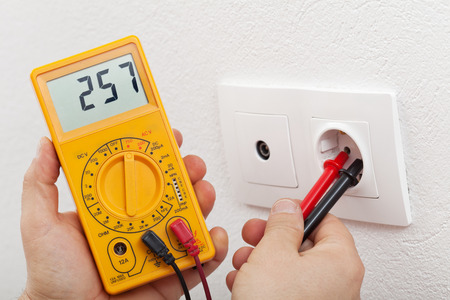 Electrician hands with multimeter - measuring voltage in electrical wall fixture photo