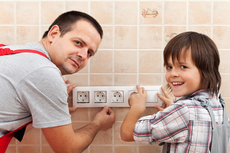 Father and son installing electrical wall fixtures together - working around the house Stock Photo - 29689290