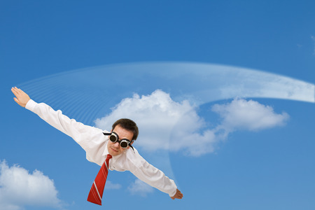 Falling or flying businessman with dark goggles and white contrail - against blue sky Stock Photo