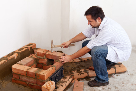 Building a masonry heater - man laying the foundation of a brick stove photo