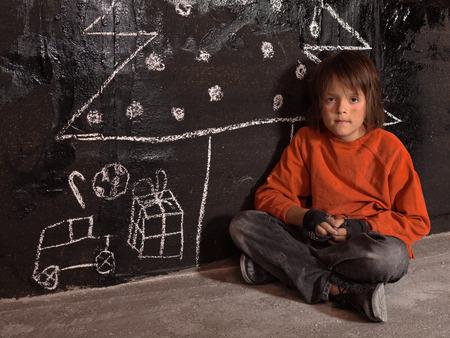 niños pobres: Pobre chico en Navidad en la calle - sentado solo Foto de archivo