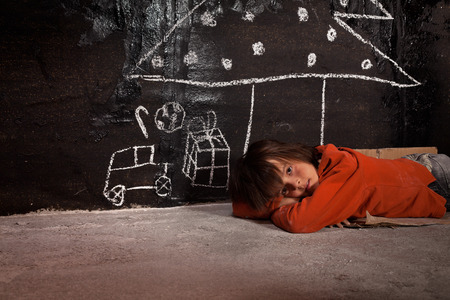 niños pobres: Pobre chico de la calle pensando de regalos de Navidad - tirado en el suelo Foto de archivo
